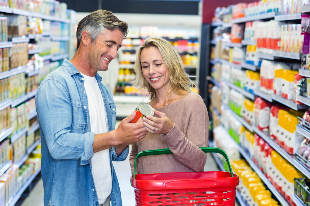 Smiling couple holding canned food at supermarket-1