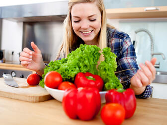 Young female cook making a fresh salad with organic vegetables