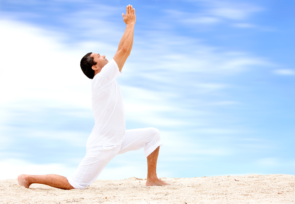 beach man doing yoga exercises in a tranquil location
